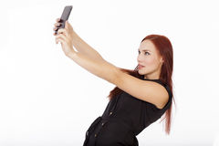 Attractive young woman with red hair takes a self portrait with royalty free stock photography