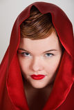 Attractive young woman in red hood Stock Images