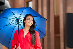 Attractive young woman in a red shirt posing with a blue umbrella Royalty Free Stock Photos