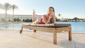 Attractive young woman in red swimsuit browsing internet on smart phone while lying on deck chair near pool side. Relaxed girl texting message and blogging stock footage