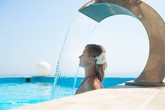 Attractive young woman refresh in pool. Young woman refresh in pool under the small waterfall Stock Images