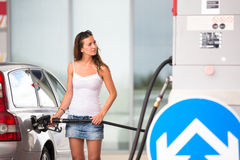 Attractive, young woman refueling her car in a gas station Stock Image