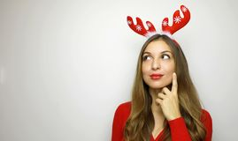 Attractive young woman with reindeer horns thinking or loooking royalty free stock image