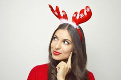 Attractive young woman with reindeer horns thinking or loooking her christmas present on gray background. Copy space. Royalty Free Stock Image
