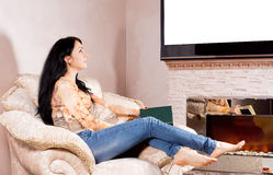 Woman daydreaming in front of the fire Stock Photography