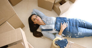 Attractive young woman relaxing on the floor. Attractive young woman relaxing on her back on the floor surrounded by brown cardboard cartons as she packs up the Royalty Free Stock Image