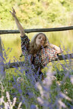 Attractive young woman is relaxing in the grass and stretching h. Erself. Sunny morning in the countryside Royalty Free Stock Image