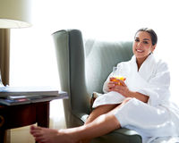 Attractive young woman relaxing at home. In her bare feet wearing a white bathrobe as she reclines in a comfortable armchair with a glass of fresh orange juice Stock Photo