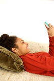Attractive young woman relaxing at home using cellphone. Close up portrait of attractive young woman relaxing at home using cellphone Stock Images