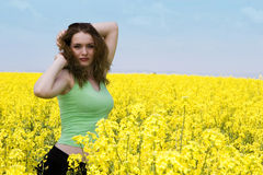 Attractive young woman relaxing outdoors. Attractive young woman in rape flower field Stock Image