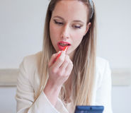 Attractive young woman in the restaurant holding lipstick and lo Royalty Free Stock Images