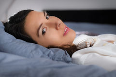 Attractive  young woman resting in bed. Low angle closeup view of a refreshed young woman resting in bed lying back on her pillow turning her head to look at the Stock Photo