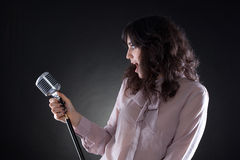 Attractive young  woman with a retro microphone Stock Photos