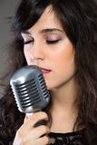Attractive young  woman with a retro microphone Royalty Free Stock Photos