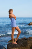 Attractive young woman on a rocky seashore. Stock Photos