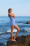 Attractive young woman on a rocky seashore. Attractive young woman in sailor's striped vest on a rocky seashore Stock Photos