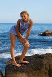 Attractive young woman on a rocky seashore. Attractive young woman in sailor's striped vest on a rocky seashore. Evening Royalty Free Stock Photography