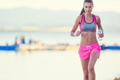 Attractive young woman running on the beach with bottle of water Royalty Free Stock Photo