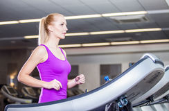 Attractive young woman running on a treadmill Stock Image