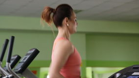 Attractive young woman running on a treadmill stock video footage