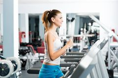 Attractive young woman runs on a treadmill Royalty Free Stock Image