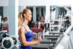 Attractive young woman runs on a treadmill Stock Photos