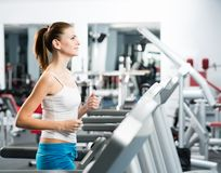 Attractive young woman runs on a treadmill Stock Photography