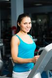 Attractive young woman runs on a treadmill Stock Images