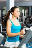 Attractive young woman runs on a treadmill Royalty Free Stock Photos