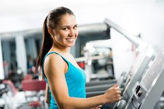 Attractive young woman runs on a treadmill Royalty Free Stock Images