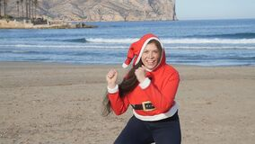 Attractive young woman in santa claus hat dancing and having fun on beach stock footage