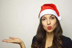 Attractive young woman with Santa Claus hat showing your product on your hand on gray background. Copy space. Attractive young woman with Santa Claus hat Stock Photography