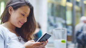 Attractive young woman sat at an outdoor cafe gently smiles as she looks at her phone Stock Image