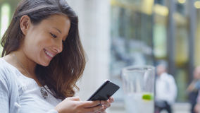 Attractive young woman sat at an outdoor cafe gently smiles as she looks at her phone Royalty Free Stock Image