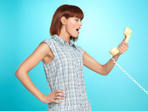Attractive young woman screaming on the telephone. Beautiful young woman, screaming on the telephone, on blue background Royalty Free Stock Photo