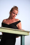 Attractive young woman at the seaside smiling down at the camera with a sensual smile as she lies on top of a wooden railing Royalty Free Stock Photos