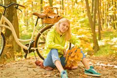 Attractive young woman in a seasonal clothes whith golden leaf. Happy young woman are preparing for autumn sunny day. Attractive young woman in a seasonal stock photography