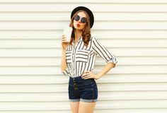 Attractive young woman sending sweet air kiss holding coffee cup in black round hat, shorts, white striped shirt on white royalty free stock photos