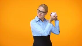 Attractive young woman shaking piggybank, bank account, financial fund, savings