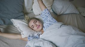 Woman stretching arms in bed stock video footage