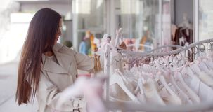 Attractive young woman shopping for clothing stock footage
