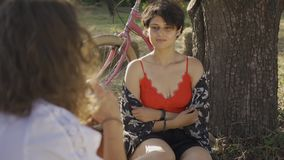 Cute young woman with short hair sitting under the tree while her friend taking photo in the garden. The bicycle. Attractive young woman with short hair posing stock video footage