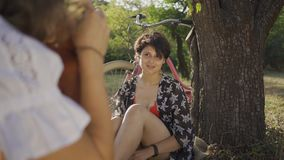 Attractive young woman with short hair sitting under the tree while her friend taking photo in the garden. The bicycle. Attractive young woman with short hair stock video footage
