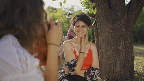 Young woman with short hair sitting under the tree while her friend taking photo in the garden. The bicycle standing. Attractive young woman with short hair stock video footage