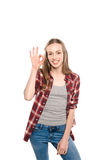 Attractive young woman showing ok sign and smiling at camera Stock Photo