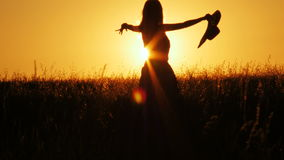 Attractive young woman silhouette dancing outdoors on a sunrise with sun shining bright behind her on a horizon. 4k shot stock video footage