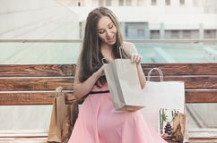 Atractive young woman sits on the bench after shopping. An attractive young woman sits on the bench after shopping and looks at purchases. Look in the package Stock Photo