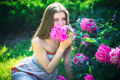 An attractive young woman sits and enjoys the scent of flowers Stock Photography