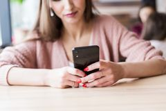 Attractive young woman sits at a table in a cafe with a cup of coffee and enjoys a laptop and smartphone royalty free stock photo