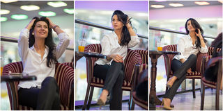 Attractive young woman sitting on armchair in shopping center. Beautiful fashionable young lady wearing white male shirt in mall. Royalty Free Stock Images